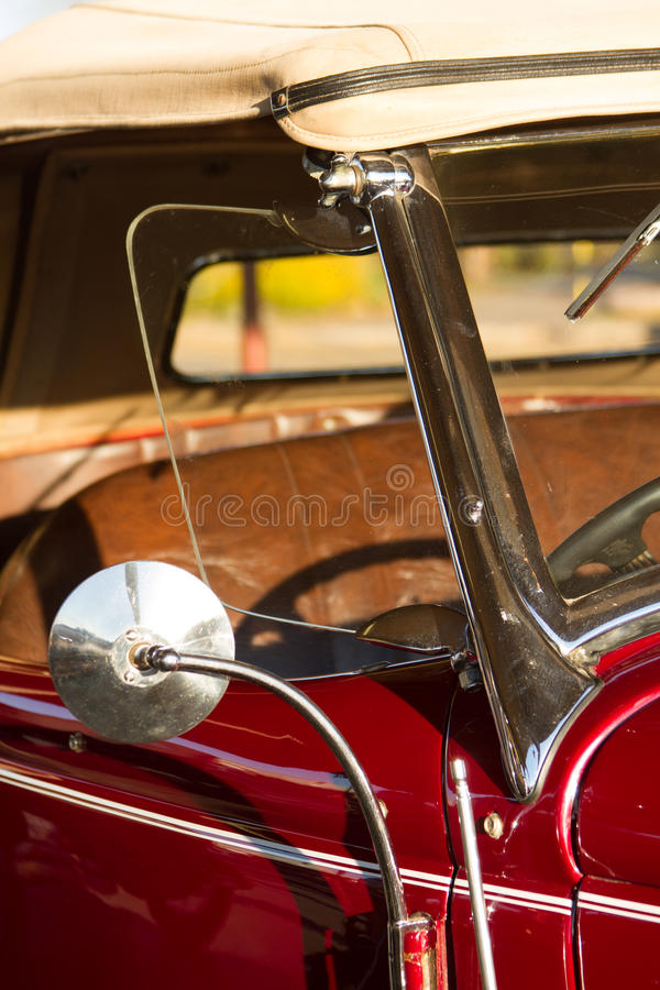 Red vintage car. Mirror side of a dark red vintage car showing the seats and steering wheel royalty free stock photo