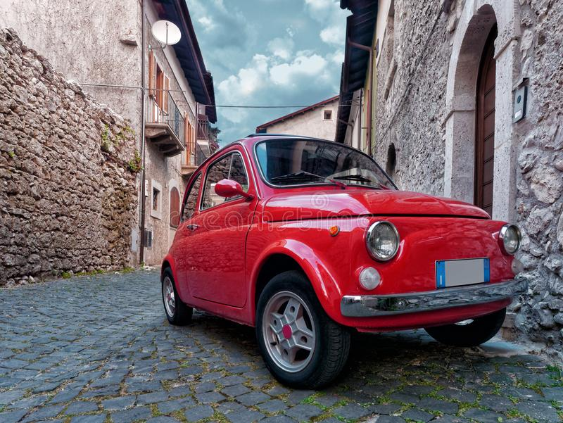 Red vintage city car parked old village. Red vintage city car parked in old village royalty free stock photography