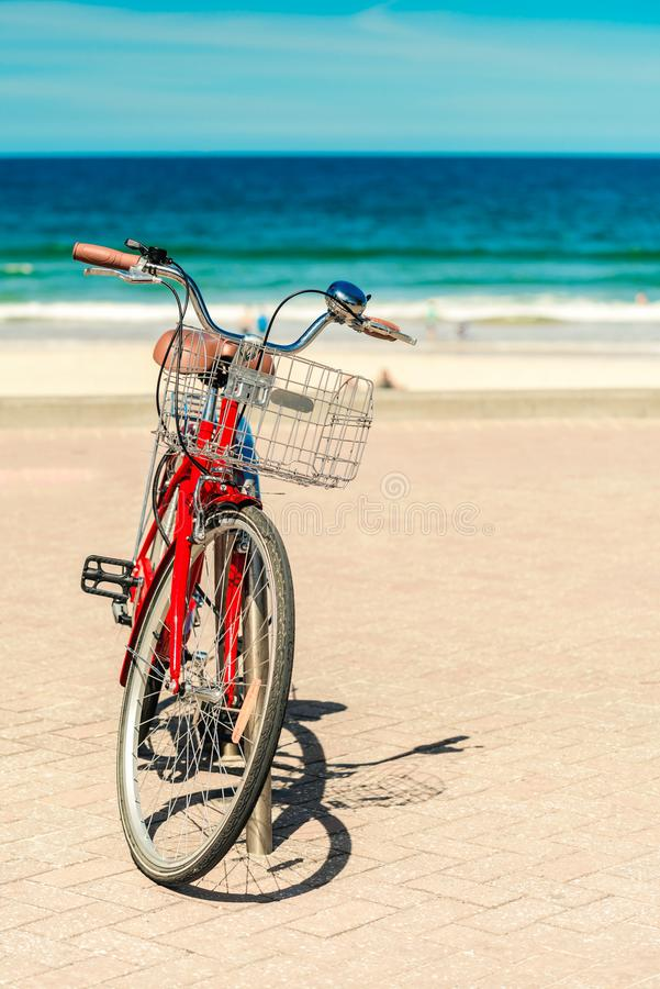 Red vintage retro styled bicycle. With basket parked at Manly Beach, Sydney, Australia royalty free stock image