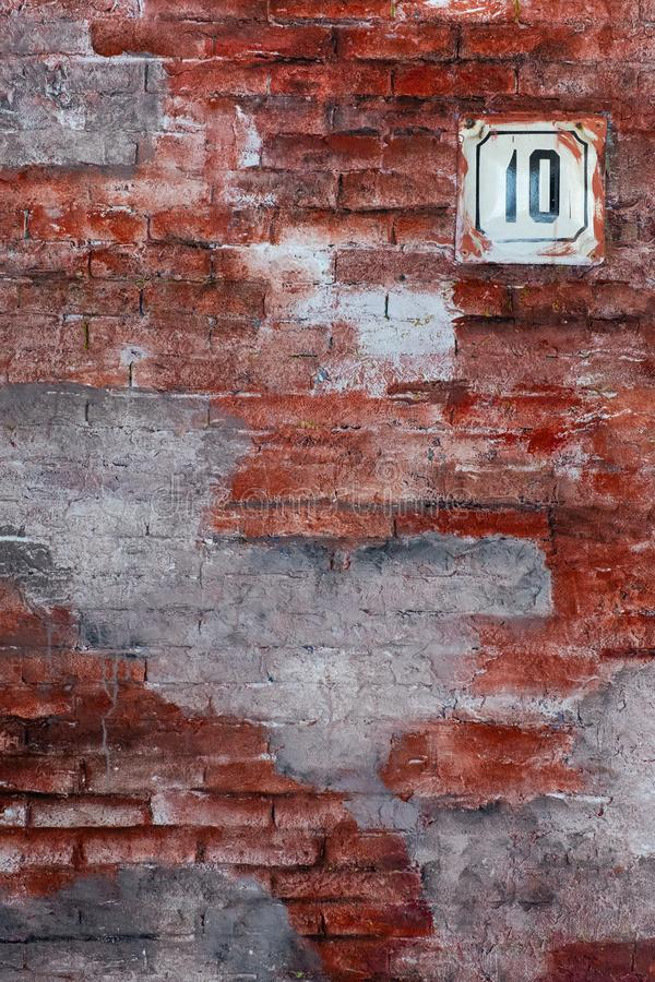 Red vintage stylish brick wall with house number plate. 10 stock photo
