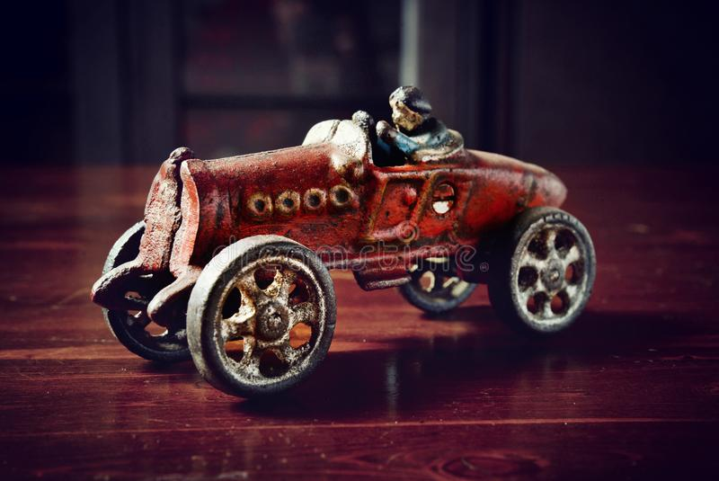 Red vintage toy car on dark wooden table.  royalty free stock photos