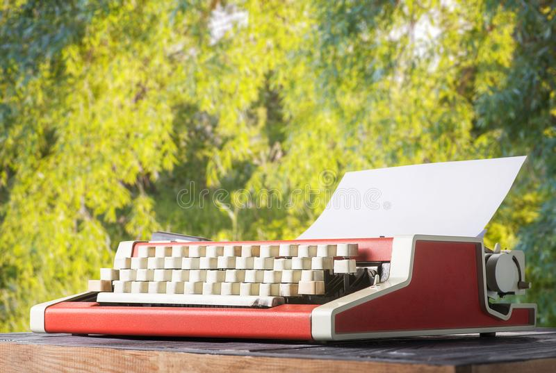 Red vintage typewriter on the table. In the garden. The writer`s work in the open air stock image