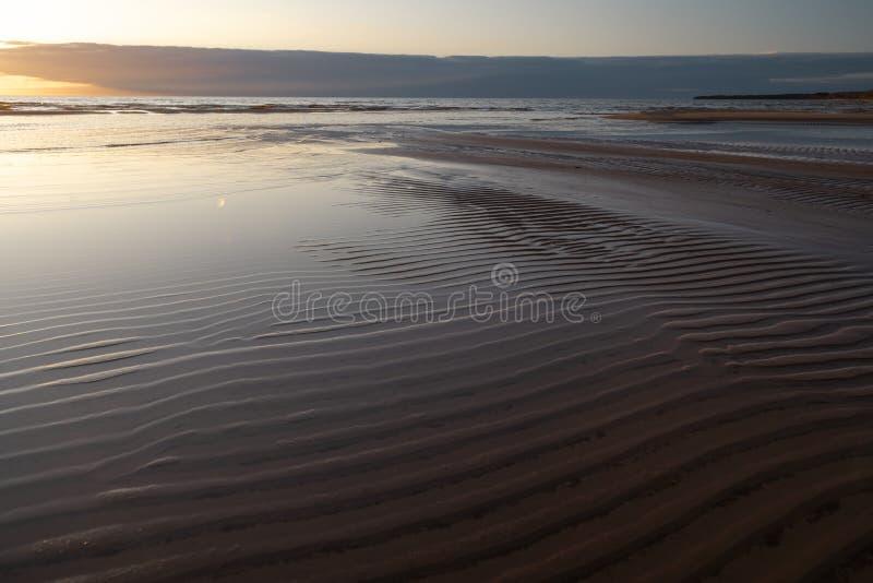 Red vivid sunset at the Baltic Sea with mirror like water - Ribbed sand and waves - Veczemju Klintis, Latvia - April 13 stock image