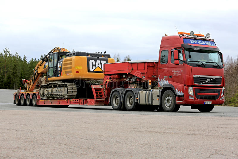 Red Volvo FH Hauls Large Excavator on Trailer royalty free stock image