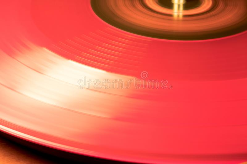 Red Vynil Disc is being played. Red binyl Disc is being played in a music player spinning royalty free stock image