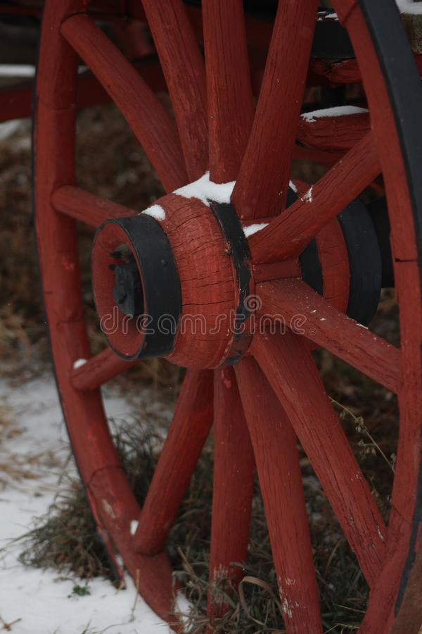 Red wagon wheel in the snow stock photography
