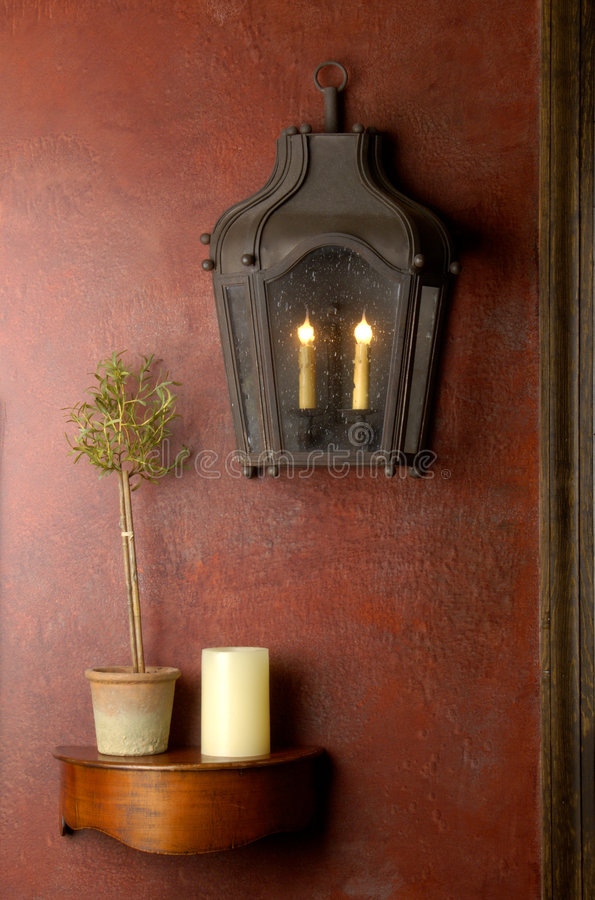 Red wall with lantern and small wooden shelf. royalty free stock photos