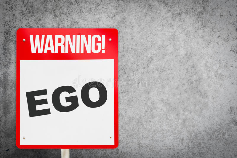 Red Warning EGO signage on cement royalty free stock images