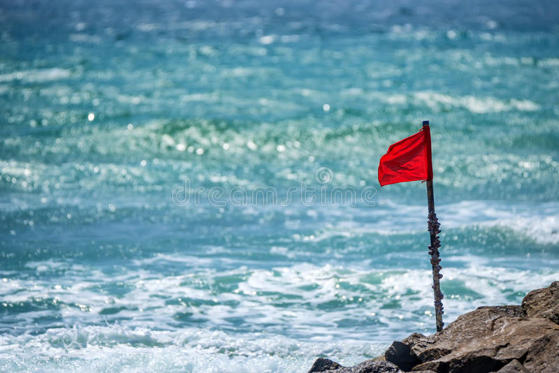 Red warning flag on beach. Showing that swimming is dangerous or prohibited royalty free stock photography