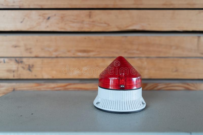 Red warning light on a control box in an industrial building in front of a wooden facade royalty free stock photography
