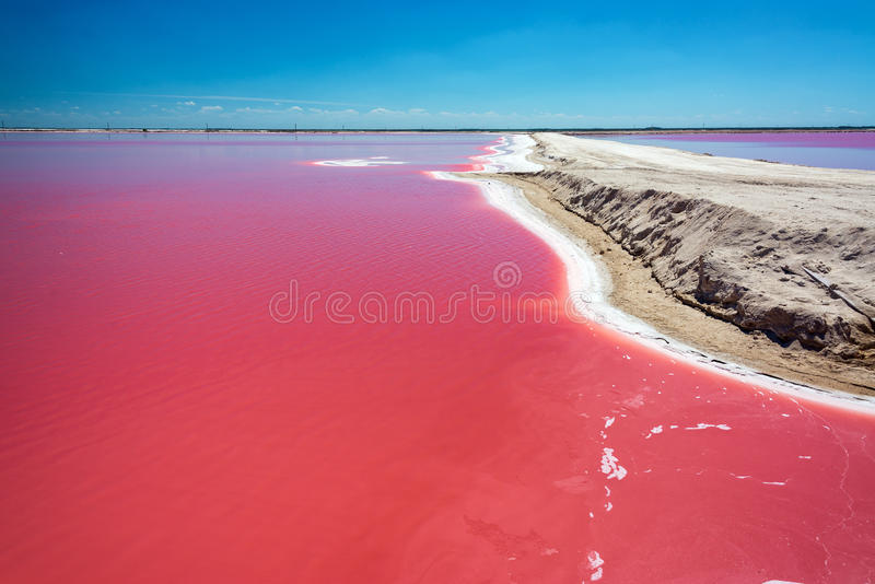Red Water and Dirt Road. Beautiful red water used in salt production with a dirt road passing by near Rio Lagartos, Mexico stock images