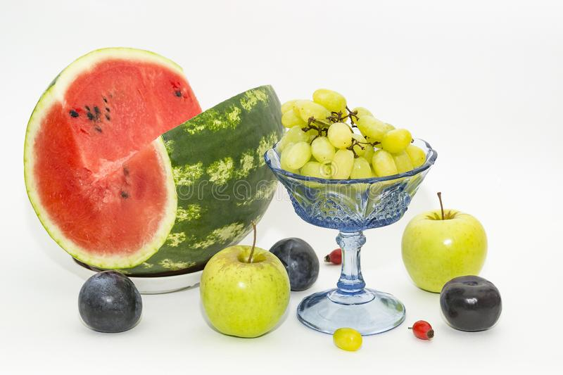 Red watermelon, green apples and blue plums royalty free stock photography