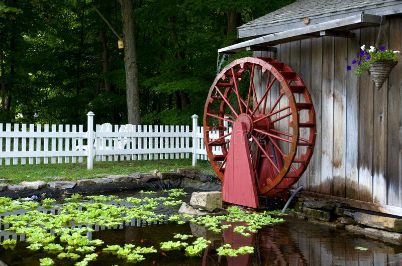 Red Watermill with Weathered Wood Building and White Fence royalty free stock image