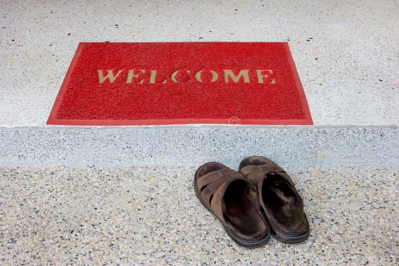 Red welcome doormat on staircase and old sandals.  royalty free stock images