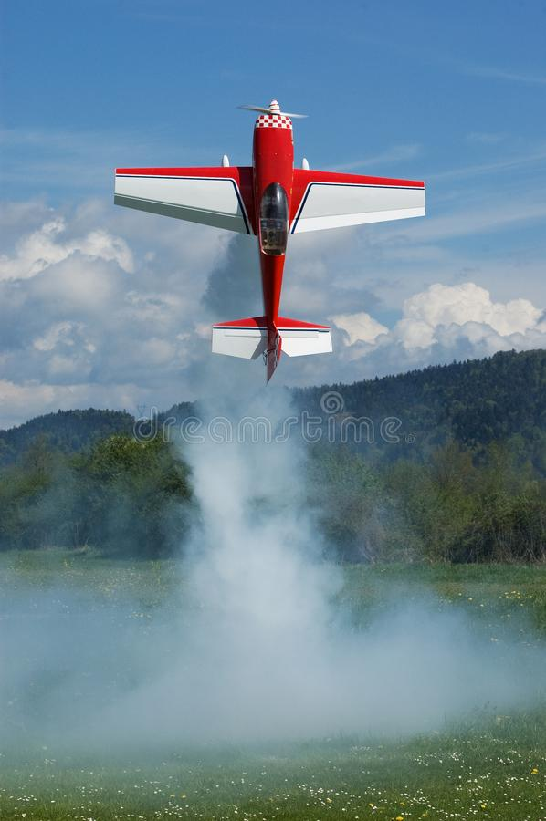 Red and white aerobatic radio controlled airplane hovering vertically. Red and white aerobatic radio controlled airplane Extra 330 hovering vertically and royalty free stock images