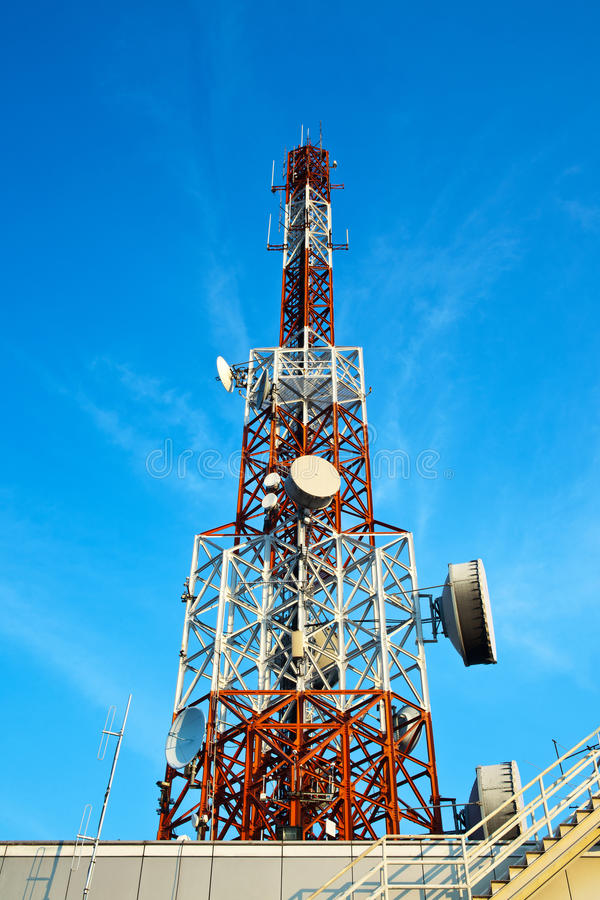 Red and white antenna (cellular tower) under blue sky. Red and white antenna (cellular tower) on the roof top under blue sky royalty free stock photos