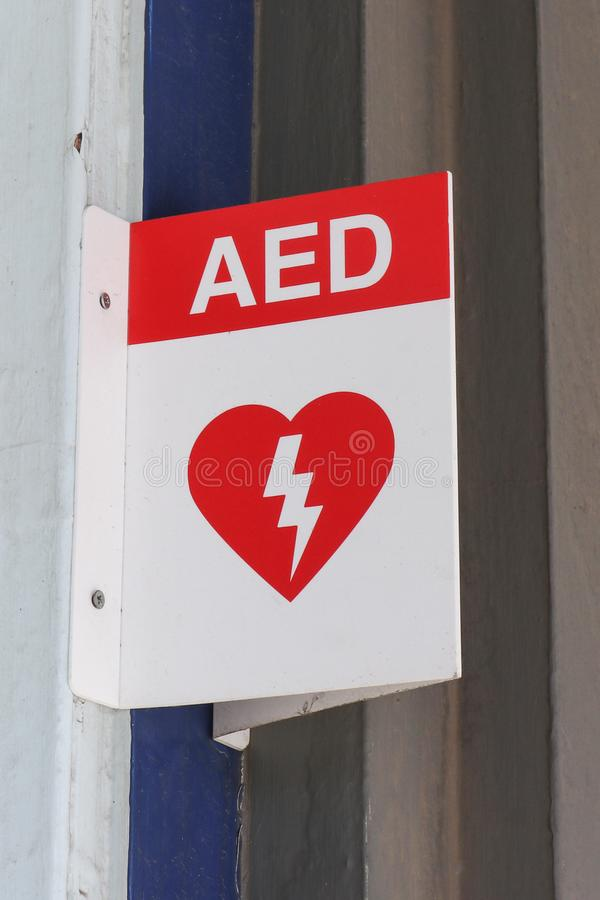 Red and white Automated External Defibrillator AED sign in a public place. A red and white Automated External Defibrillator AED sign in a public place royalty free stock image