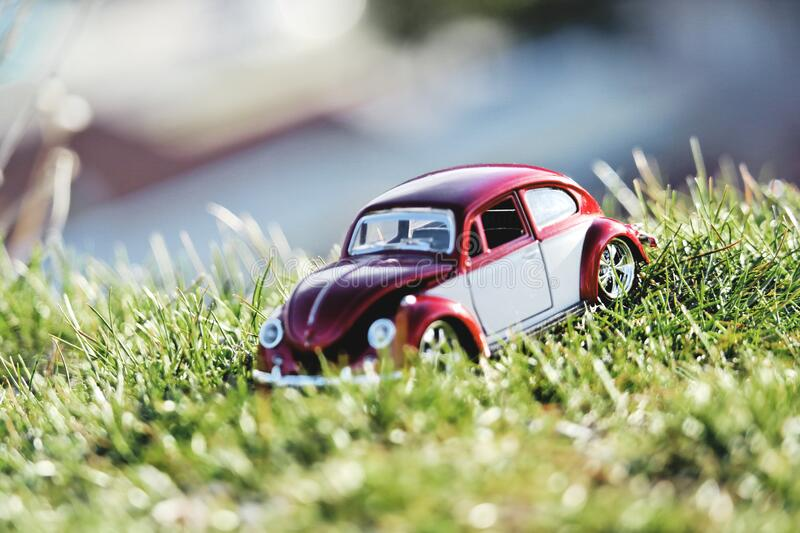 Red and White Beetle Car Toy on Grass Field in Bokeh Photography royalty free stock photos
