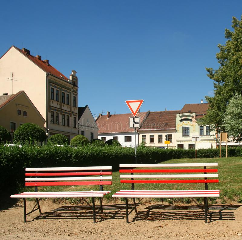 Red-and-white benches are sitting in the centre of small village in Europe. Contrasting and noticeable scene.  stock photos
