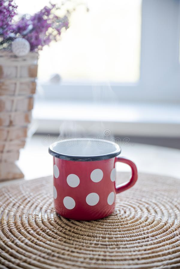 Red, White, and Black Ceramic Mug on Table stock photo