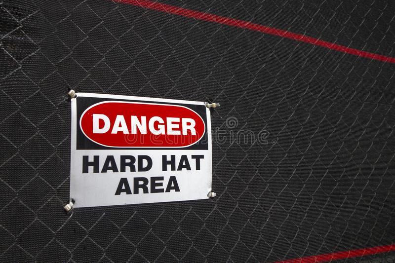 Red white black danger hard hat area sign on net covered fence. Danger hard hat area sign on a fenced in area covered with black mesh stock image