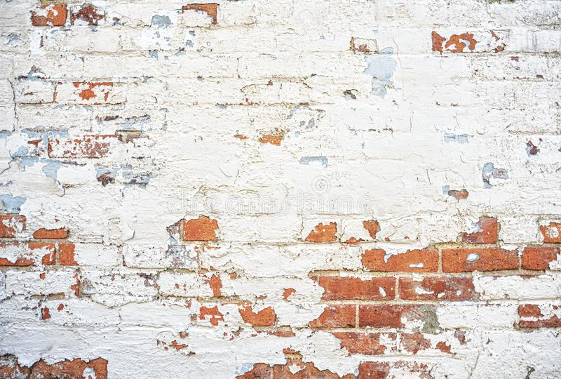 Terra cotta red brick wall white and blue peeling paint background royalty free stock images
