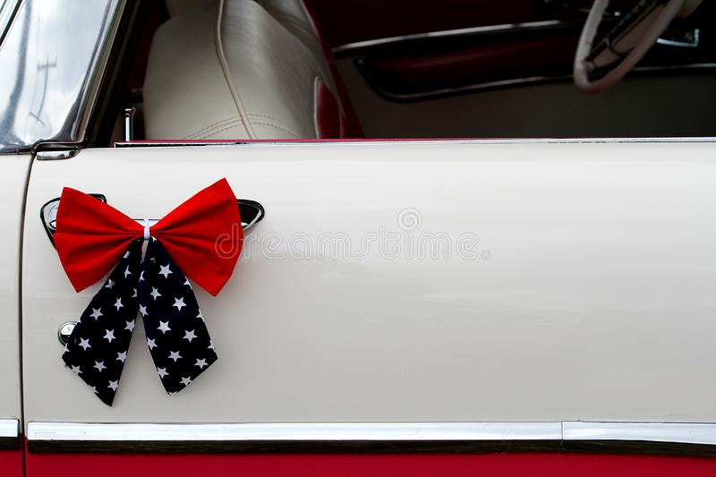 Patriotic red, white and blue bow on classic American car. stock photography