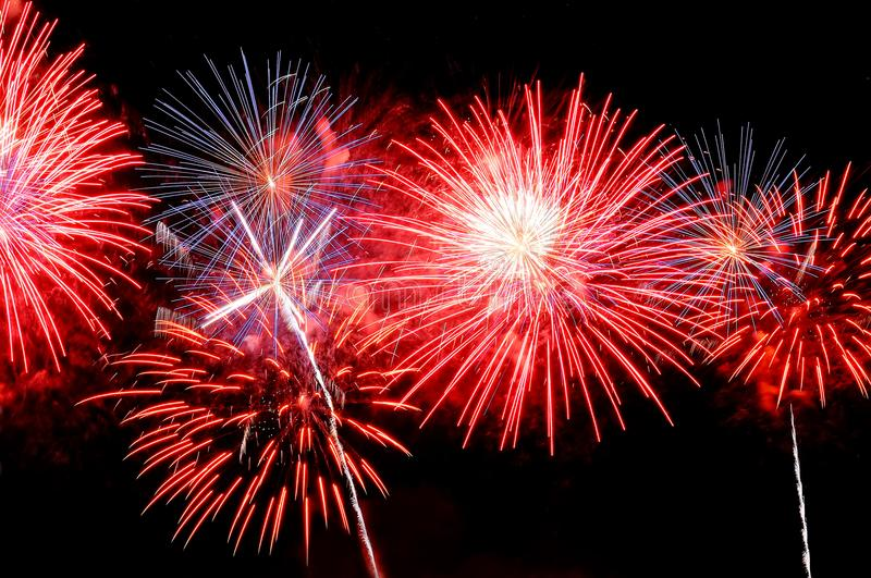 Red, white and blue fireworks display on dark sky background royalty free stock photography