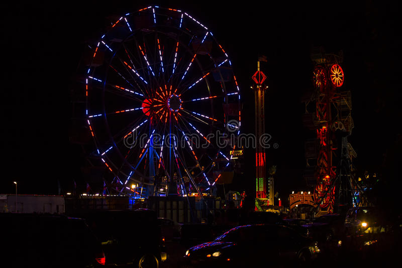 Red, White and Blue July 4th Festival Ferris Wheel at Night. Bright red, white and blue lights rotate around on this festive 4th of July festival ferris wheel stock photos