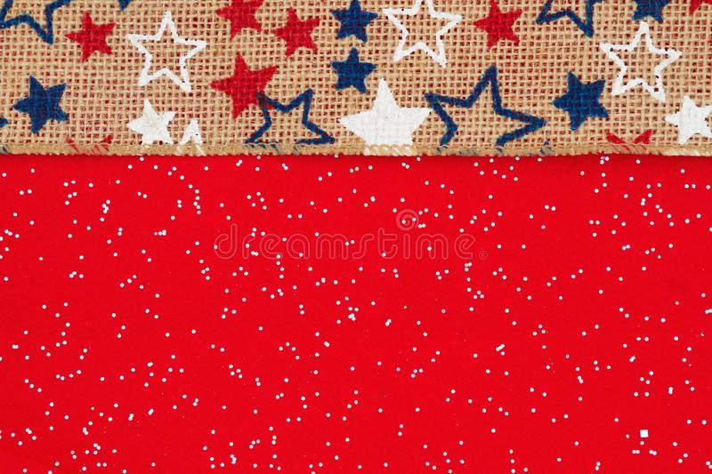 Red, white and blue stars on burlap on a red felt sparkle background. With copy space for your message royalty free stock photo