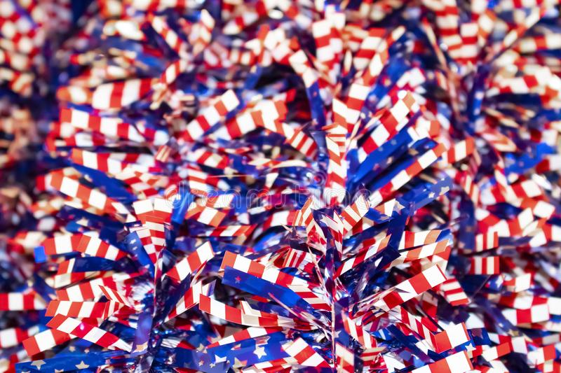Red white and blue stars and stripes tinsel - selective focus on front with blurred bokeh - festive patriotic background. A Red white and blue stars and stripes royalty free stock image