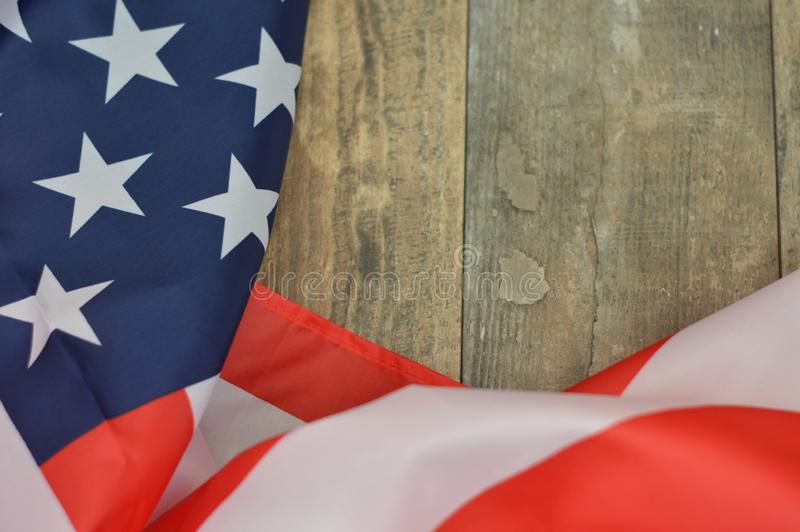 Star spangled banner against a wooden background. The red white and blue stars and stripes on wood not flying but laid down stock image