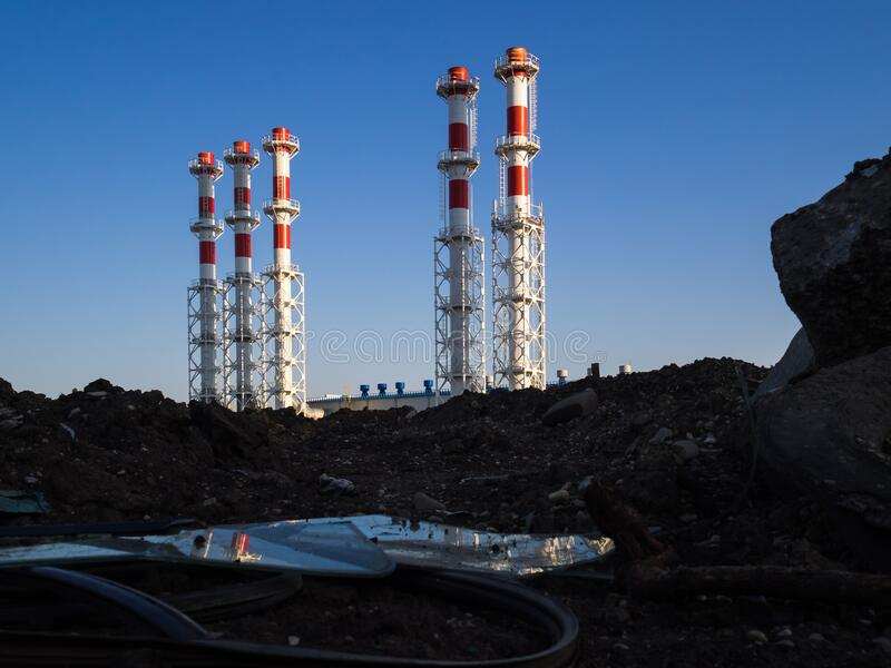 Red-and-white boiler room chimneys against a blue sky. Mountain of stones and debris and pipes boiler station. Environment royalty free stock images