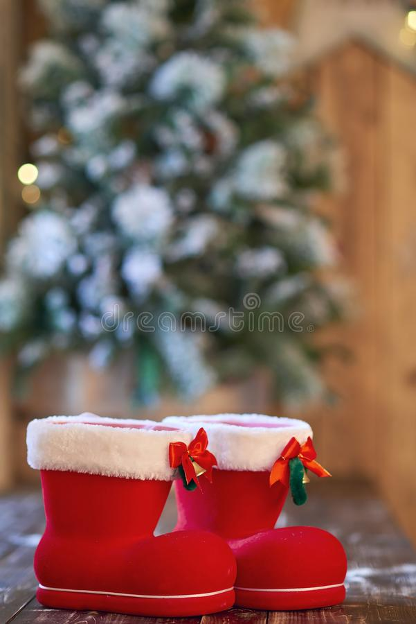 Red with white border Christmas boot near Christmas tree on wooden background.  stock photo
