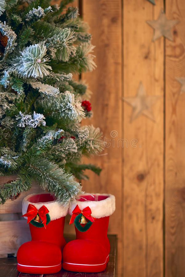 Red with white border Christmas boot under Christmas tree on wooden background with stars.  royalty free stock photo