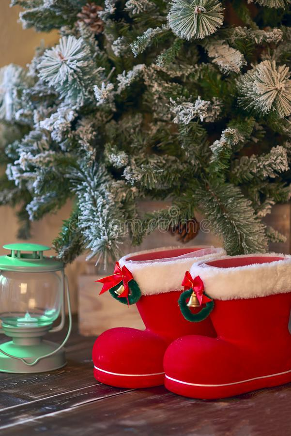 Red with white border Christmas boots and green lantern under Christmas tree.  stock photos