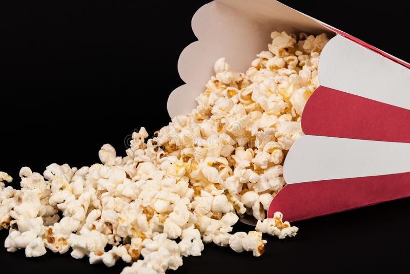Popcorn spilled on black background. Red and white box of popcorn spilled and isolated on black background. Movie and Food concept. Studio shoot royalty free stock image