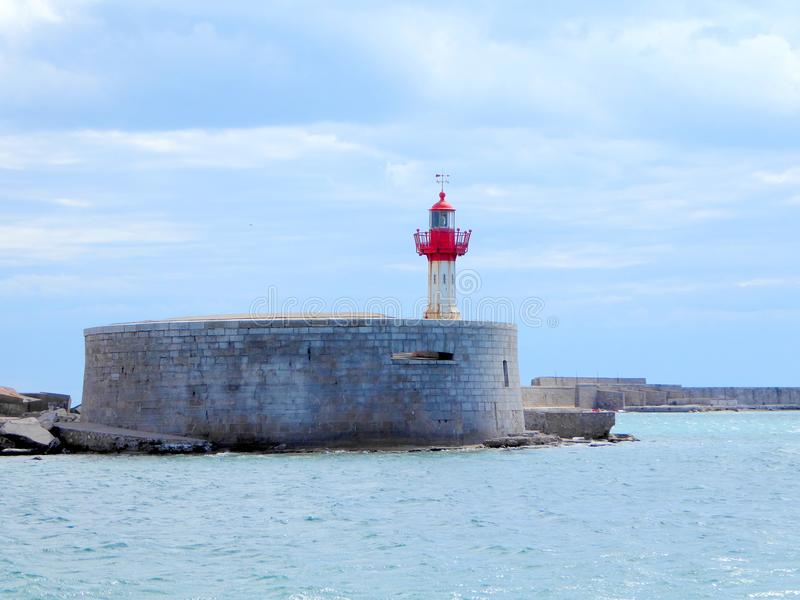 Red and white breakwater lighthouse. The red and white breakwater lighthouse at the port of Sete in the south of France stock images