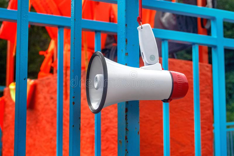 Red and white bullhorn for the public announcement against the background of orange life jackets.  stock images