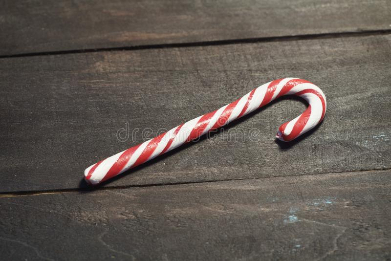 Red and white candy canes on a background of dark wooden planks. Close up. Christmas photo vector illustration