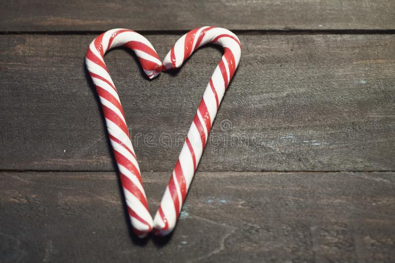 Red and white candy canes forming a heart on a background of dark wooden planks. Close up. Christmas photo vector illustration