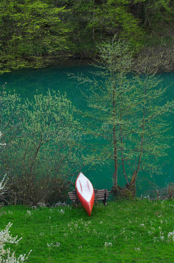 A red and white canoe resting by the river royalty free stock image