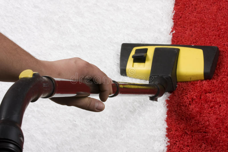 Red and white Carpet vacuuming stock image