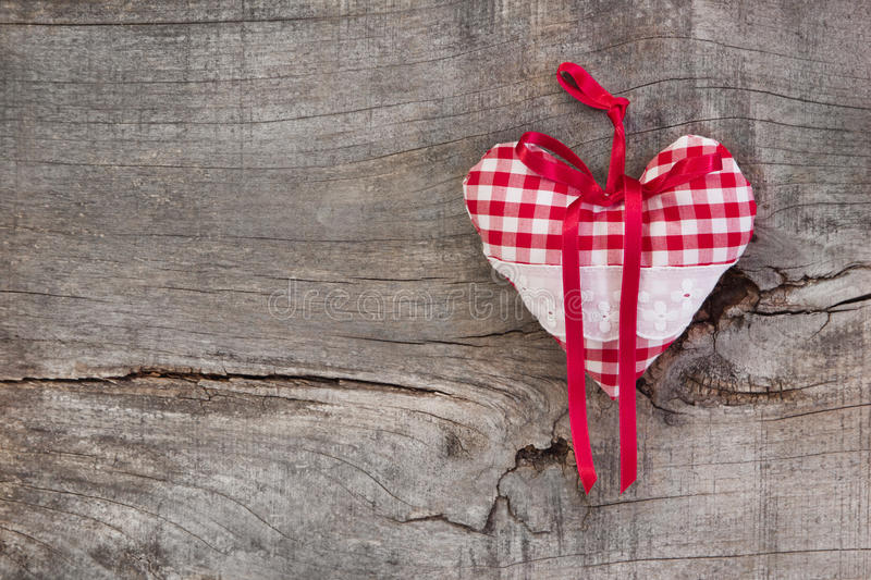 Red/white checkered heart shape hanging on a wooden background f royalty free stock image