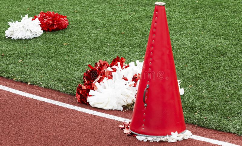Red and white cheerleading megaphone and pop poms stock photos