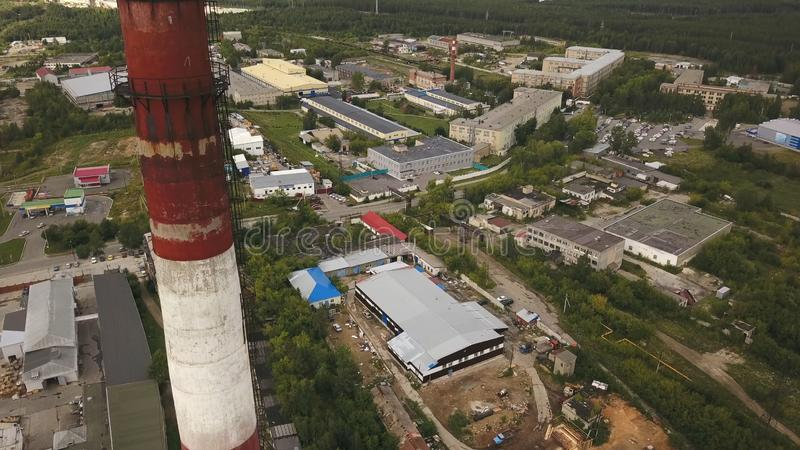 Red and white chimney-stalk above the industrial zone, hangars and other factory buildings surrounded by green forest royalty free stock photo