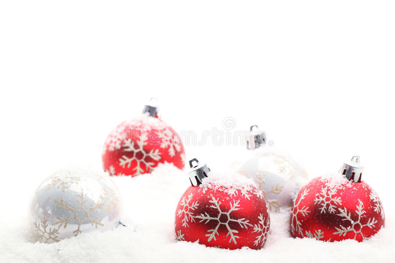 Red and white christmas balls in snow flakes royalty free stock photo