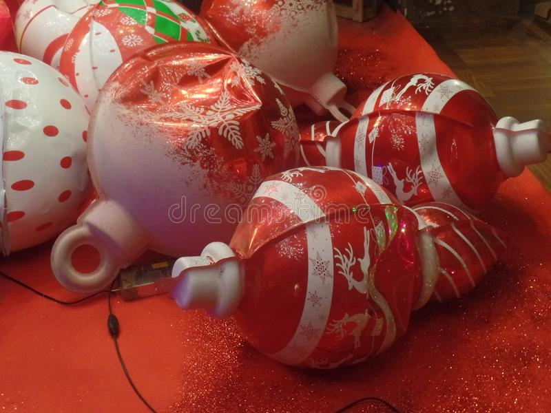 Red and white Christmas bauble decorations. Against a red background stock photo