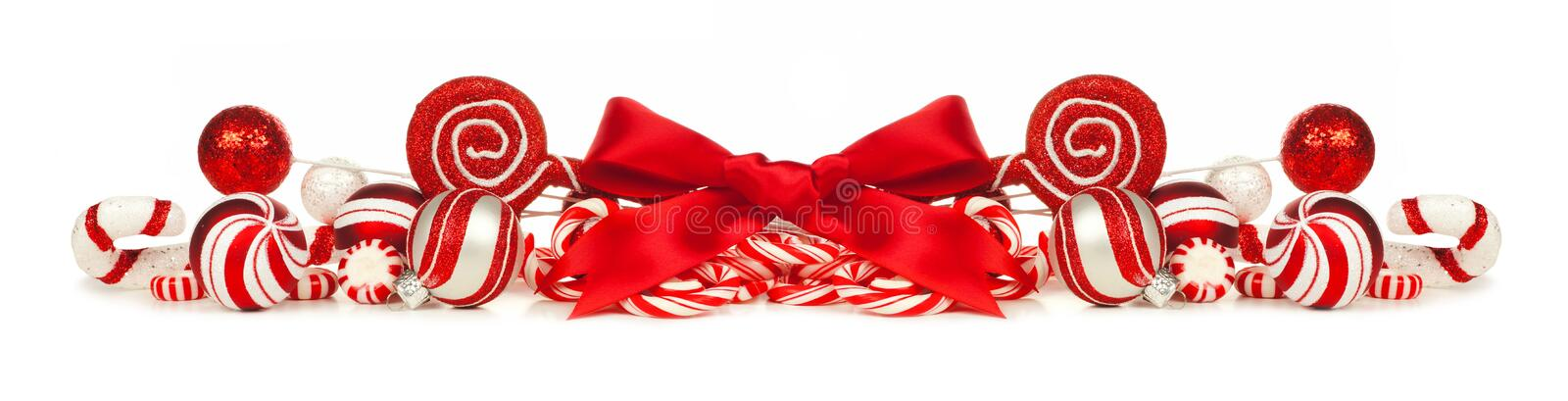 Red and white Christmas baubles, bows and candy cane border. Christmas border of red and white baubles, bows and candy canes isolated on a white background