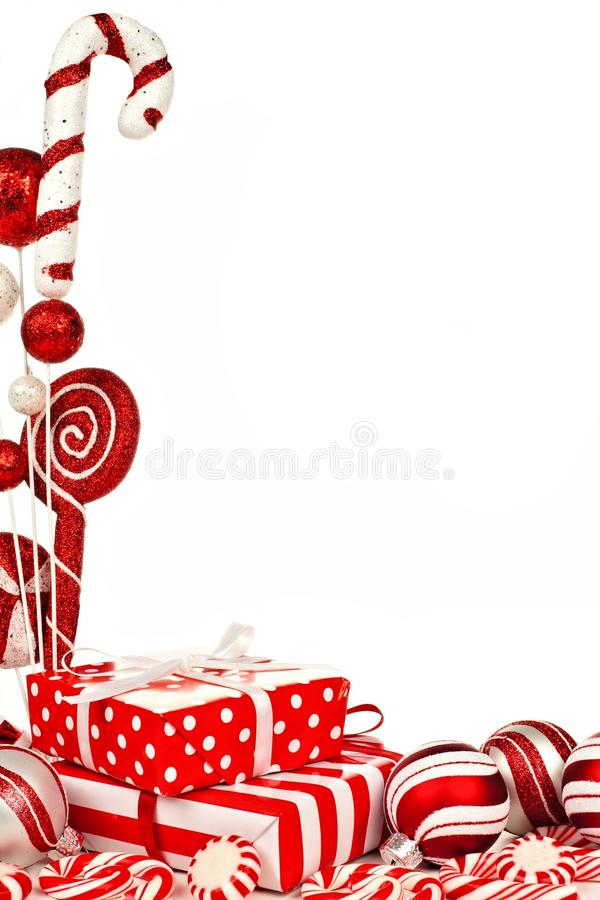 Red and white Christmas border with gifts, baubles and candy. Red and white Christmas corner border with gifts, baubles and candy against white background stock photo